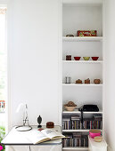 White shelf with small bowls and CD-s, in front of it a small table with reading lamp