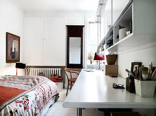 Long desk, shelf above in bedroom, bed with colorful bedspread