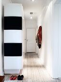 Black and white cupboard in the hallway with light wooden floorboards