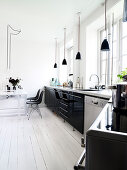 Black high-gloss kitchen and dining area in an old apartment with white plank floor