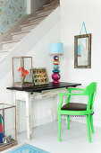 A table lamp on an old wooden table with a green armchair in front of a staircase in the corner of room