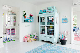 Light blue display cabinet with books, seat cushions, and a little suitcase on top