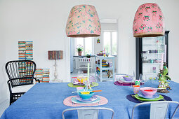 A table laid for Asian food with a pendant lamp with a retro lampshade above it