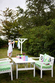 Table and seats made of white lacquered wood, with green and white cushions in the garden, in the background woman at the clothes horse