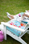White deck chair with colorful pillows in the garden