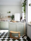 Modern stool in front of the kitchen island in a classic kitchen with a checkerboard floor
