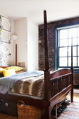 An antique double bed with a wooden frame, a built-in wardrobe and a window in a bedroom with exposed brickwork