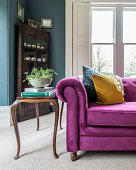 Old side table next to pink velvet sofa in classic living room