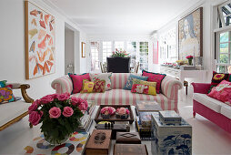 View past books and boxes on coffee table to pink-and-white striped sofa