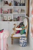 Cushions on antique armchair and chine pot on floor in front of white bookcase