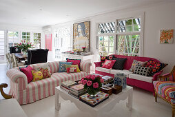 Sofas with scatter cushions around white coffee table holding books, boxes and vase of roses in open-plan living room