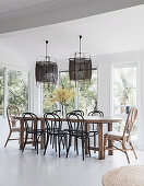 Wooden dining table with bentwood chairs in front of a window, bamboo hanging lamps above
