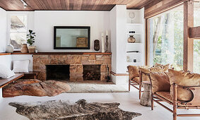 Sandstone fireplace, piece of rock in front, vintage leather armchair and animal fur rug in the living room