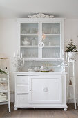 Vintage decorations on white dresser with glass-fronted top cabinet
