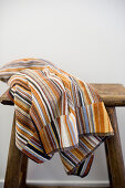 Towel striped in earthy shades on wooden stool