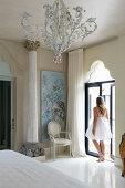 Woman wearing white summer dress in Mediterranan bedroom