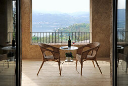 Wicker armchairs and delicate table on Mediterranean terrace with view of landscape