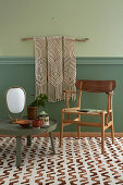 Macrame wall hanging above chair and low round table on patterned carpet