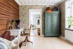 Study with log-cabin wall and wallpaper with botanical pattern