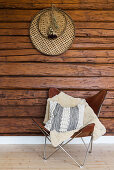 Leather Butterfly Chair against rustic log-cabin wall