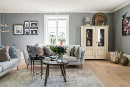 Mixture of old and new furnishings in living room with grey walls