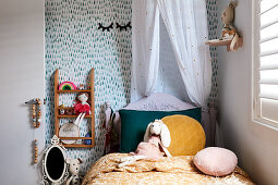 Bed with canopy and patterned wallpaper in girl's bedroom