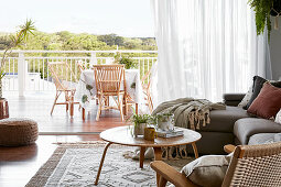 View from living room with sofa and coffee table onto terrace