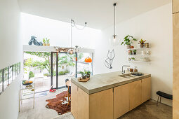 Kitchen island with wooden fronts and concrete worksurface in split-level house