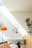 Shaft of light falling on white wall with wall decal in open-plan kitchen