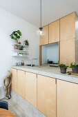 Fitted kitchen and island counter with wooden fronts and concrete worksurface and figurine of girl in corner