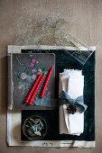 Rote Kerzen auf altem Notizbuch, Glasvase mit Blütenzweig, Weißer Stoff mit blauem Band und getrocknete Blätter