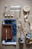 Bügelflasche, Teelichter, Stoffband, Kännchen mit Trockenzweig und Fischmesser auf Holzschale
