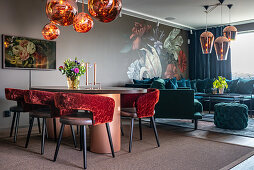 Velvet-upholstered furniture and wallpaper with large floral pattern in living-dining area