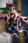 Basket of plums, ribbon and Echinaceas