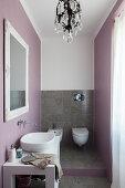 Toilet, tiled floor and pastel lilac walls in elegant bathroom