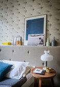Upholstered bead headboard with ledge against retro wallpaper