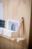 Shelf suspended from leather straps on plywood organiser