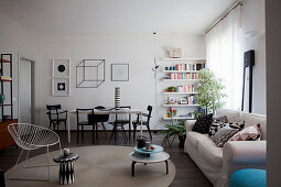 Polstersfofa mit Kissen, Beistelltisch und Sessel, im Hintergrund Essbereich und Bücherregal