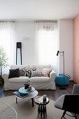 Hussensofa mit Kissen vor Fenster und Beistelltische auf rundem Teppich