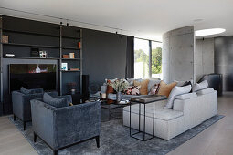 Velvet armchairs and sofa in elegant living room in shades of grey