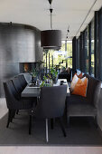 Dining table with upholstered chairs and bench in black, open-plan interior