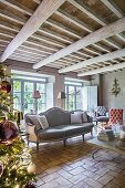 Christmas tree and grey sofa in living room of renovated farmhouse