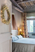Double bed in bedroom with festive wreath on door