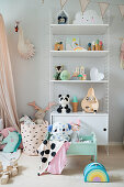 Offenes Wandregal mit niedlicher Kinderdeko in pastellfarbenem Mädchenzimmer