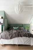 Bed below sloping ceiling with green knee wall and wood-clad ceiling