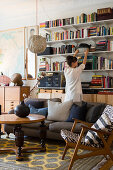Woman in front of bookcase in eclectic, vintage-style living room