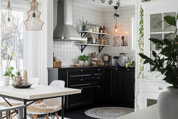 View across dining table into open-plan kitchen with black units