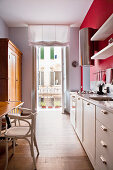 View through long, narrow kitchen with white counter against red wall in small apartment