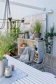 Herbstlich dekorierte Terrasse mit Tisch, Korbstühlen und Holzregal