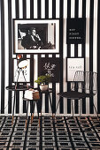 Chair and side table in black-and-white seating area with pictures on striped wallpaper